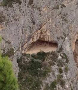 La grotta come una macchia di colore giallo-rossiccio è visibile a metà della parete rocciosa tra Tamborio e la Sementella
